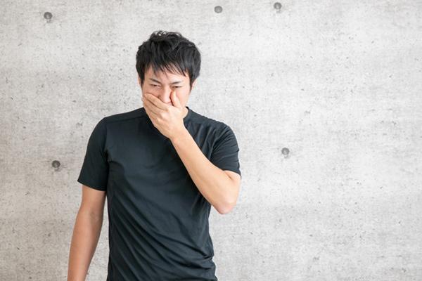 鼻をふさぐ男性