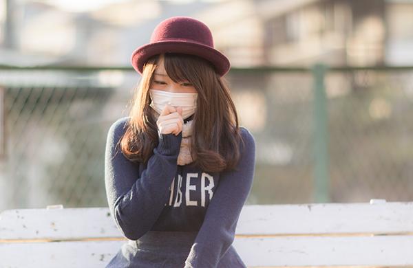 マスクを手で押さえる女性