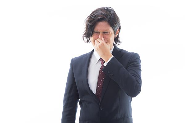 思わず鼻を押さえるスーツ姿の男性