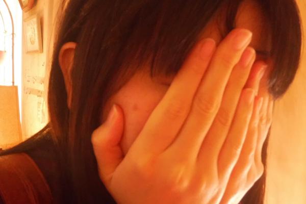 手で顔を隠して恥ずかしがる女性