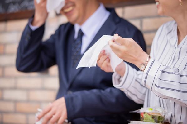 顔から流れ出る汗を拭き取る男性と見つめる女性