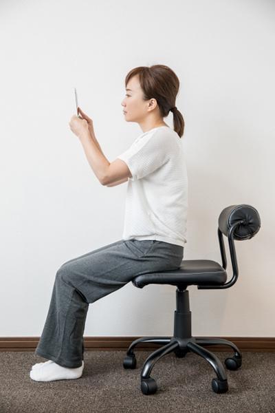 椅子に座って正しい姿勢でスマホを見つめる